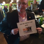 Oshawa Mayor John Henry hold sign saying ask me about 100 Men Oshawa
