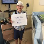 Young boy with Epilepsy holding thank you sign
